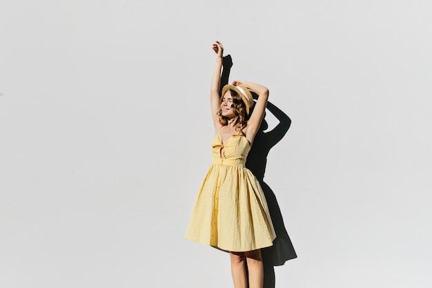 晴れた朝に楽しんでいるレトロなドレスの魅惑的な女性。麦わら帽子と黄色の衣装でリラックスした金髪の女性の屋外写真。
