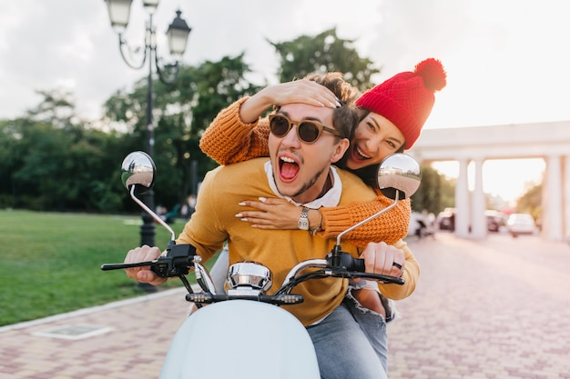 Enchanting lady in red hat touching boyfriend's forehead with smile while he drives scooter
