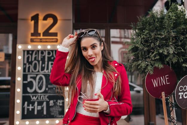 Incantevole signora in giacca rossa in posa con la lingua fuori per strada
