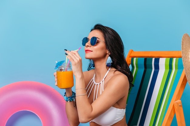 Enchanting lady in sunglasses drinking orange juice