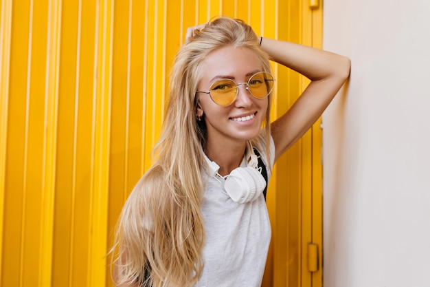 Enchanting long-haired laughing girl in yellow sunglasses.