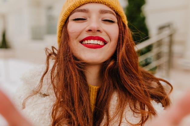 目を閉じて笑っている帽子をかぶった魅惑的な長髪の女性。冬の幸せを表現する熱狂的な生姜少女の屋外写真。