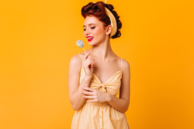 하드 캔디를 들고 매혹적인 핀 업 소녀. 노란색 공간에 고립 된 롤리팝 잠겨있는 생강 여자의 스튜디오 샷.