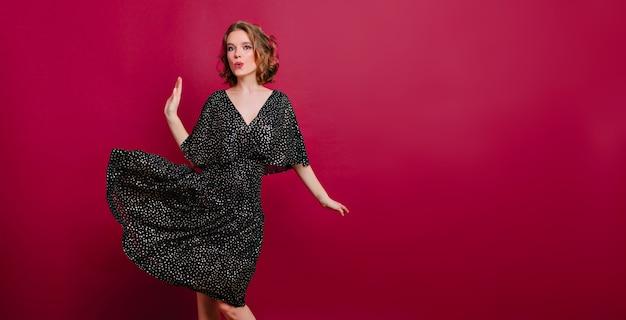 Incantevole ragazza sottile in eleganti scarpe tacco alto ballando su sfondo bordeaux