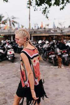 Incantevole ragazza abbronzata indossa abiti lavorati a maglia in posa su sfocatura dello sfondo della strada.