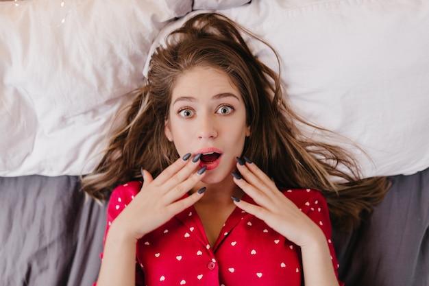 ベッドで身も凍るように驚きの感情を表現する魅惑的な白人少女。かっこいい若い女性の頭上の肖像画は赤い服を着ています。