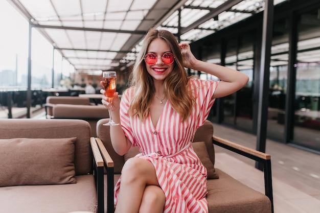 Incantevole ragazza bianca in occhiali da sole rosa in posa con il bicchiere di vino in mano. ridendo affascinante donna in abito a righe rilassante nella caffetteria.