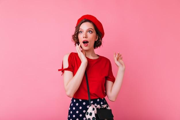 Incantevole ragazza bianca con tatuaggio guardando qualcosa. ritratto di splendida donna francese in berretto isolato.