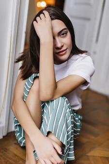 Incantevole donna bianca con i capelli castano scuro che si rilassa a casa. ritratto dell'interno dell'affascinante ragazza europea seduta sul pavimento.