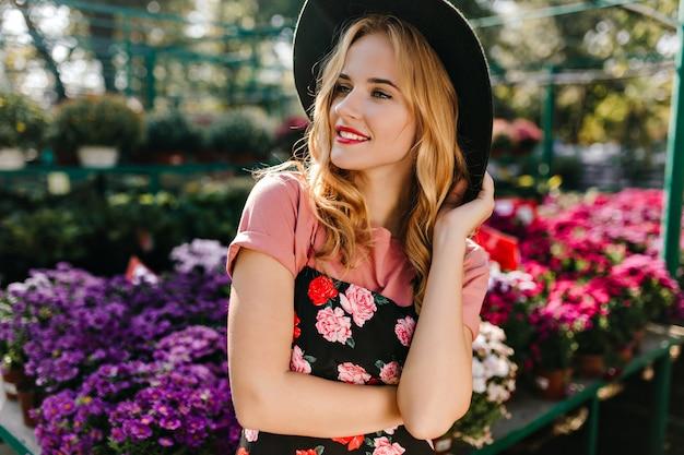 自然の中に立っている帽子をかぶった魅惑的な女性。オレンジリーに時間を費やしている巻き毛の物思いにふける女性モデル。