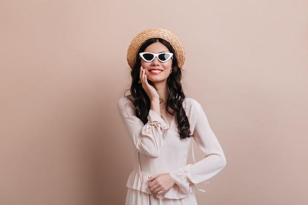 ベージュの背景で笑っているサングラスの魅惑的な女性。麦わら帽子で満足しているブルネットの女性の正面図。