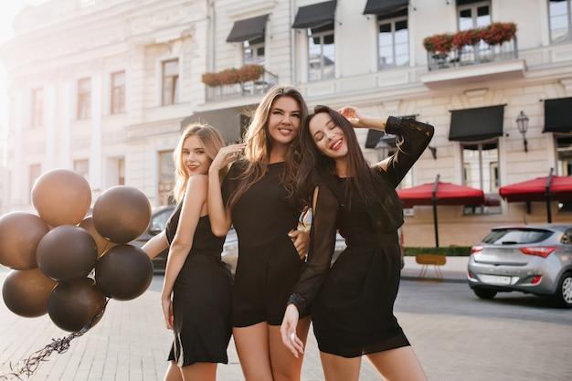 Очаровательная женщина с темными волосами наслаждается встречей с сестрами и нежно улыбается