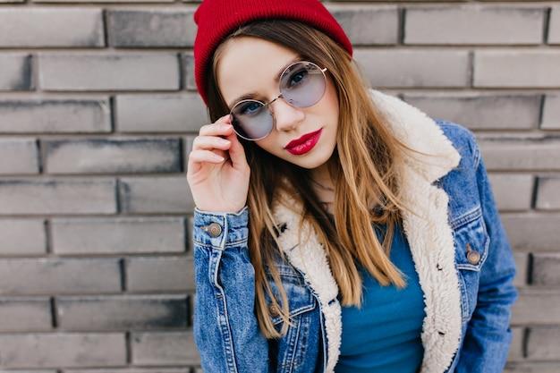 벽돌 벽 앞에서 포즈를 취하는 블루 라운드 안경에 매혹적인 젊은 아가씨. 하얀 피부를 가진 즐거운 백인 여자의 야외 촬영은 데님 재킷을 입는다.
