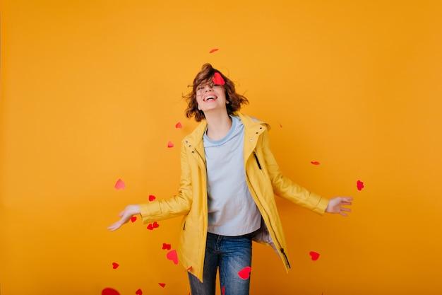 Incantevole giovane donna in abiti autunnali divertendosi e buttando fuori i cuori. ragazza adorabile in jeans che si preparano per il giorno di san valentino.