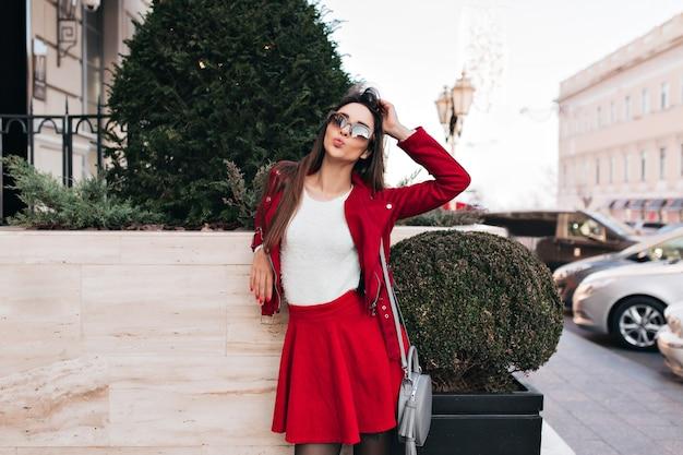 Incantevole giovane donna in gonna rossa in piedi sulla strada con borsa grigia