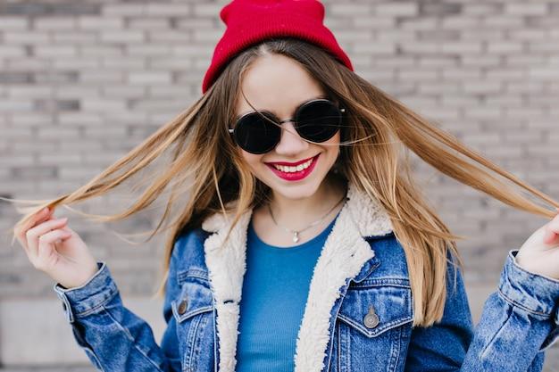 春の日を屋外で過ごす明るいメイクで魅惑的な若い女性。レンガの壁の前で笑っているデニムジャケットの美しい白人の女の子の写真。