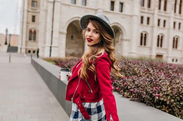 Incantevole giovane donna con acconciatura ondulata guardando sopra la spalla mentre si cammina per la città europea