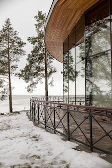 Закрытая стеклянная терраса современного ресторана на берегу озера в красивом зимнем снегу.