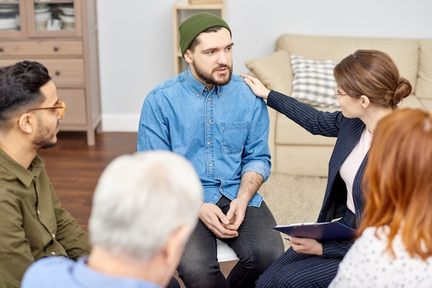 Encouraging depressed patient at group therapy session Premium Photo