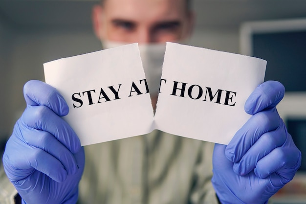 End of covid-19 pandemic. victory in fight against pandemic. cure corona virus. man tearing card with hashtag stay at home. exit from self-isolation to freedom.