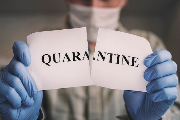 End of covid-19 pandemic. victory in fight against pandemic. cure corona virus. man tearing card with word quarantine. exit from self-isolation to freedom.