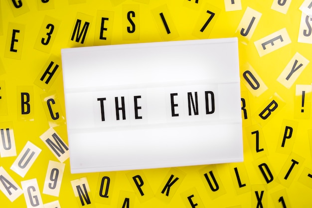 The end message on lightbox on scattered letters background of plastic alphabet