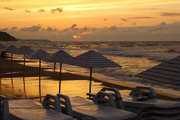 Конец пляжного сезона собрал шезлонги и зонтики на мокром песке в штормовую погоду на закате