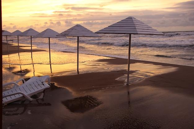 Конец пляжного сезона зонтики и шезлонг на мокром песке у пляжа в штормовую погоду на закате
