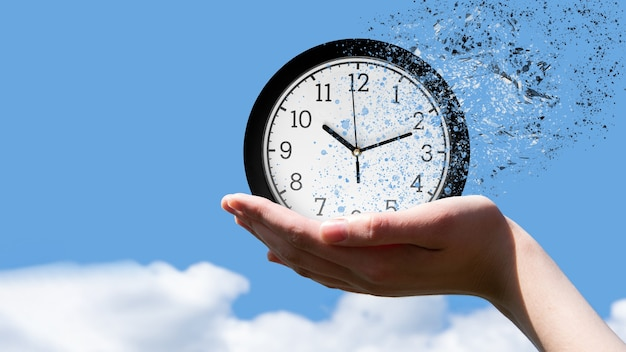 End of time or flight of time concept. female hand holding a classic round clock falling into small pieces against a blue sky, front view, copy space