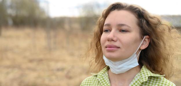分離と検疫コロナウイルスcovid-19コンセプトを終了します。 30歳の若いヨーロッパの女性が顔から医療用マスクを外し、屋外の自然の中で新鮮な空気を吸いました