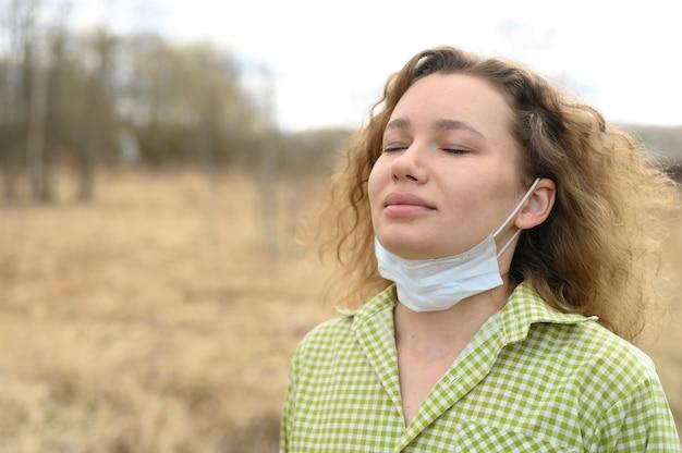 分離と検疫コロナウイルスcovid-19コンセプトを終了します。若いヨーロッパの女性は彼女の顔から医療用マスクを取り外し、屋外の自然の中で新鮮な空気を呼吸します
