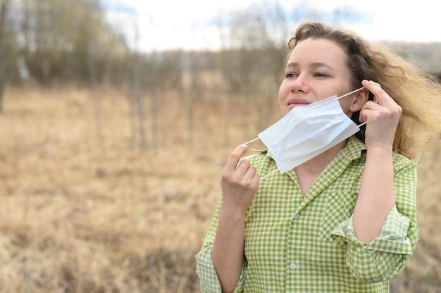 分離と検疫コロナウイルスcovid-19コンセプトを終了します。若いヨーロッパの女性は彼女の顔と屋外の自然の中で新鮮な空気を呼吸から医療マスクを削除します