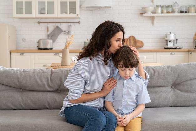 Окончание семейной ссоры: мать чувствует себя виноватой, обняв непослушного сына после того, как отругала его за плохое поведение