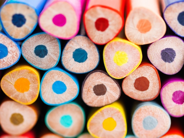 Ends of colorful watercolor pencils. school supplies background.