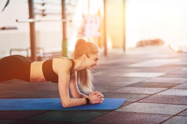 持久力運動。ジムで板運動をしているフィットネス女性