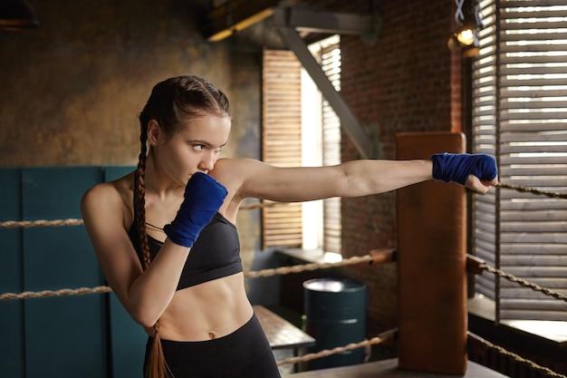 耐久性、強さ、護身術、武道の概念。パンチに取り組んで、屋内で運動する美しい決意の若い女性キックボクサー