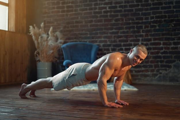 지구력 운동. 강한 근육 질의 남자 연습 푸시 업 운동 집에서 백인 운동 선수는 실내에서 판자 훈련을