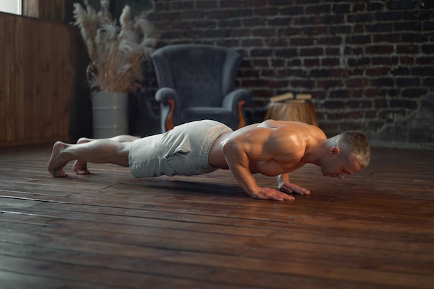 Endurance workout. strong muscular man practicing push ups exercise at home interior caucasian athlete do plank training indoors