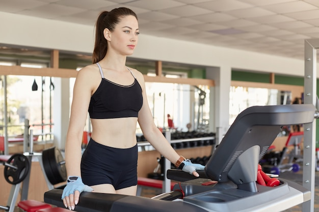 Enduring confident young lady starts training on treadmill, does cardio exercises, feels confident. athletic slender girl wears black top, black tight shorts, light blue gloves, watch.