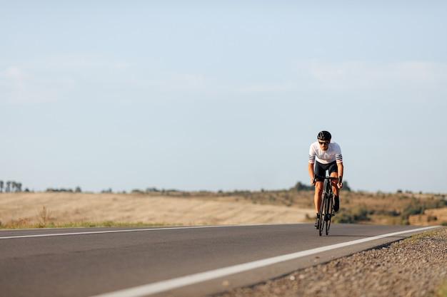 아침 시간 동안 자전거에서 연습하는 보호 헬멧에 젊은 남자를 영속