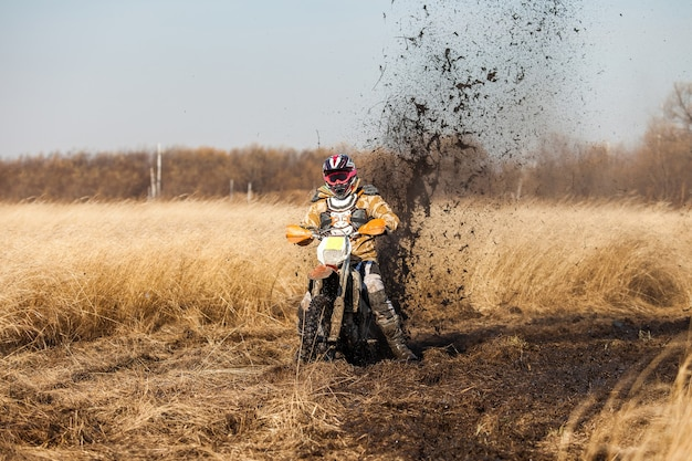 Enduro bike rider in a field with dry grass in autumn. the motorcycle skids and makes a lot of mud splashes
