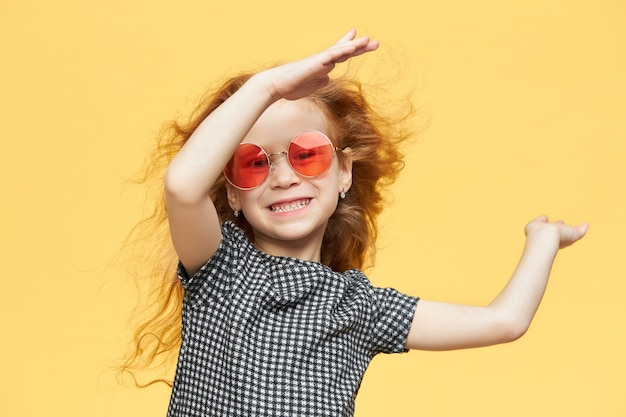 Energetic acitve cheerful little girl with wavy ginger hair looking with broad radiant smile, enjoying nice time