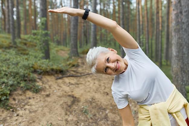 Energetic active middle aged female warming body before running, posing against pine trees