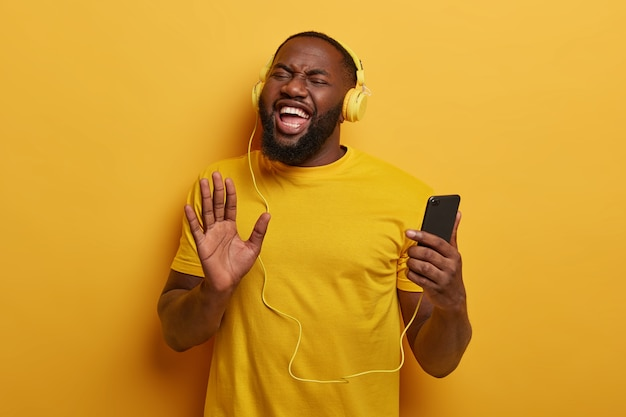 Energetic afro american man pulls palm toward camera, uses smartphone and headset for listening radio or audio tracks in playlist, boosts mood with favorite song