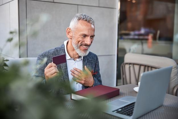 Dar-red 플라스틱 카드를 들고 노트북 앞에서 손으로 몸짓을하는 활기찬 노화 남자