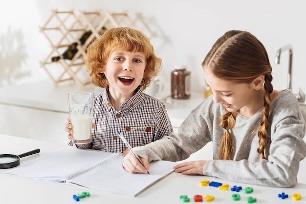 활기차고 재미 있습니다. 함께 시간을 보내고 테이블에 앉아있는 동안 기뻐 보이는 호기심 많은 긍정적 인 에너지 아이들
