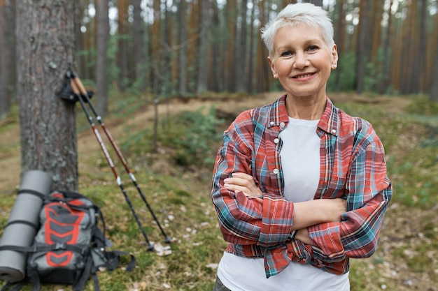 Energetic attractive middle aged woman hiker posing outdoors, choosing active lifestyle, traveling alone with backpack and nordic poles for walking, keeping arms crossed and smiling at camera