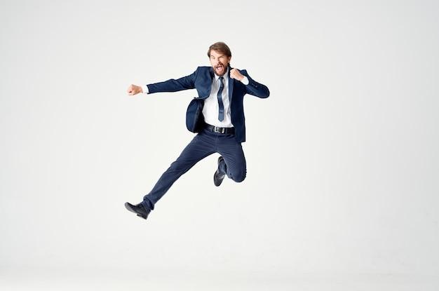 青いスーツを着たエネルギッシュなビジネスマンが明るい空間の成功の喜びの感情に飛び上がる