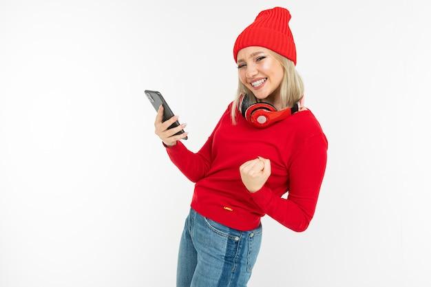 白い背景の上で踊るスマートフォンとヘッドフォンを持つエネルギッシュなカリスマ的なブロンドの女の子。