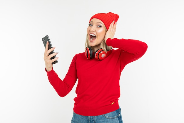 Energetic charismatic blonde girl with a smartphone and headphones dancing on a white background